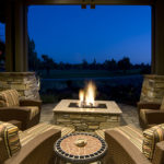 Deck with fire pit, outdoor furniture, and with a beautiful evening setting.